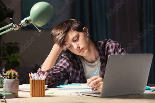 Leinwanddruck Bild Teenager doing homework at table in evening