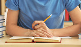 Teenager boy doing homework in library, closeup - 209769715