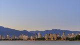modern city with mountains and tall buildings, a huge blue sky with a sunset glow - 209771759