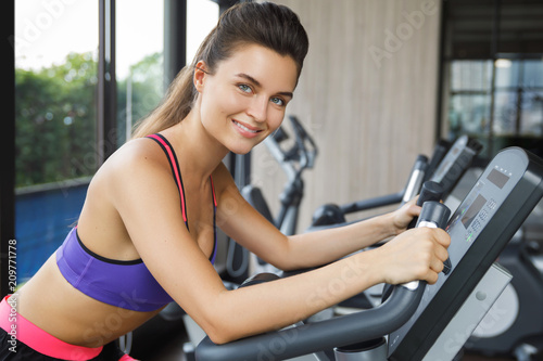 Poster Woman on stationary bike in the gym