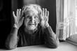 Leinwanddruck Bild - Portrait of cheerful old woman holding wrinkled hands near her ears. Black and white photo.