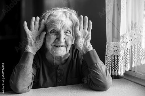 Leinwanddruck Bild Portrait of cheerful old woman holding wrinkled hands near her ears. Black and white photo.