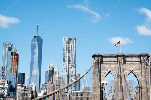 Fotobehang New York View of lower Manhattan. Wall Street area, and the Brooklyn Bridge with American Flag on top from Brooklyn, New York. View of lower New York from Brooklyn side.