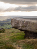 Rock formation near stanage edge in the peak district of great britain with columns of light shining through the clouds - 209778185