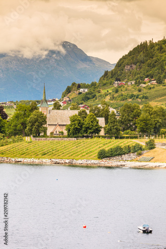 Foto Murales Mountains and fjord with village Norway.
