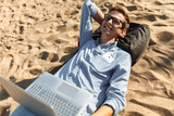 Young guy with glasses, lying on the sand, working on his laptop on the beach, against the sea, working on vacation, suitable for advertising, text insertion