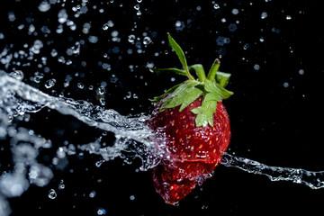 juicy red strawberry in water splash on black background