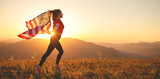 happy woman with flag of united states enjoying the sunset on nature - 209790129