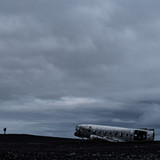 Man looking at plane wreck in iceland