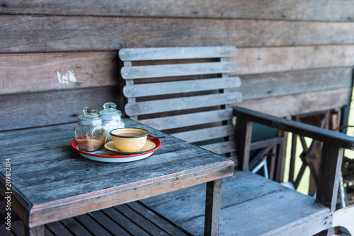 Foto Murales Traditional Thai coffee on wooden table and empty wooden chair