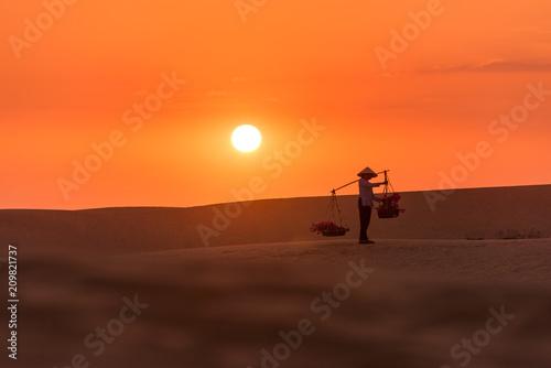Aluminium Oranje eclat Woman carrying flower basket at sunset in Mui Ne sand dune, Vietnam