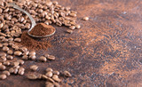 Black roasted coffee grains and ground coffee in spoon lie on a copper table.