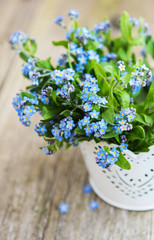 Forget-me-not flowers in small metal bucket