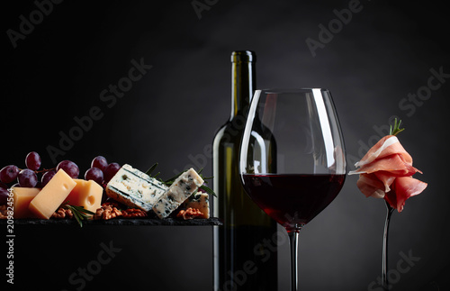 Glass of red wine with various cheeses , fruits and prosciutto. - 209824564