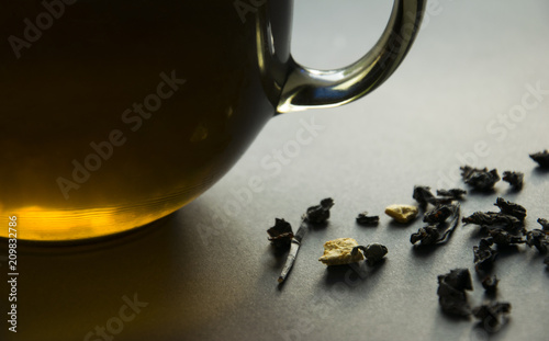 A cup of tea and scattered tea leaves on a dark background