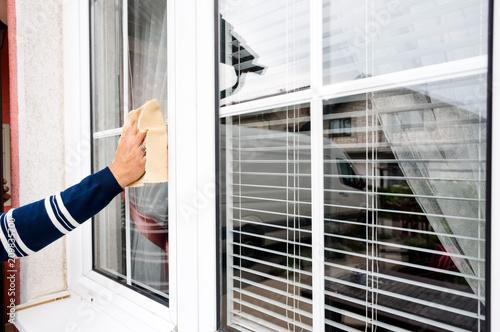 Foto Murales woman hand cleaning white pvc window