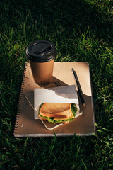 close up view of notebooks, sandwich and coffee to go on green grass