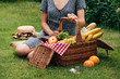 cropped image of woman sitting on green grass at picnic and touching wicker basket
