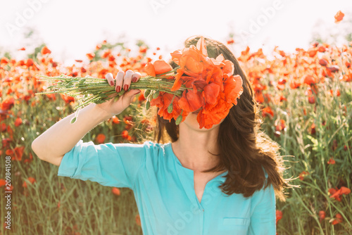 Fototapeta Girl covered her face with bouquet of poppies.