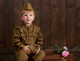 children boy are dressed as soldier in retro military uniforms with flask sitting on old suitcase, dark wood background, retro style - 209844348