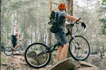 selective focus of male extreme cyclist on mountain bike talking to friend with bmx in forest