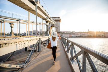 Young woman traveler walking on the famous Chain bridge during the sunset in budapest, Hungary
