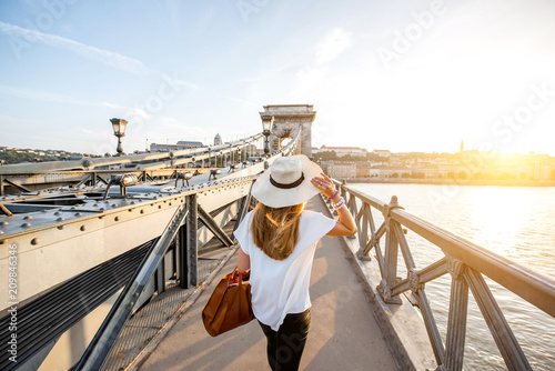 Young woman traveler walking on the famous Chain bridge during the sunset in budapest, Hungary - 209846346
