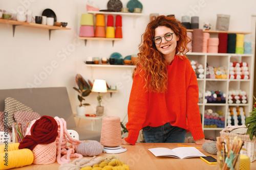 Sweter oversize. Kreatywnie entuzjastyczna dziewczyna jest ubranym eleganckiego czerwonego barwionego oversize pulower wydaje czas w sztuki studiu