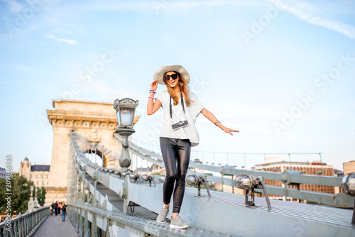 obraz lub plakat Young woman tourist walking on the old Chain bridge during the sunset traveling in the Budapest