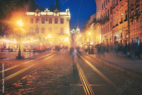 A crowd of people moving on the old european city night street defocused blurred abstract image - 209846982