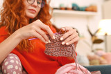 Wavy hair. Red-haired appealing woman with red long wavy hair feeling very good while knitting beautiful baby socks