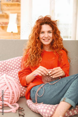 True relax. Smiling beautiful red-haired student feeling extremely relaxed while leaning on sofa back