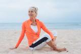 ältere frau sitz am strand und dehnt sich nach dem sport