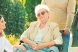 Senior woman in wheelchair with nurse from care home and her friends outdoors - 209848127