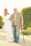 Senior man with cane and nurse from care home walking in park - 209848190