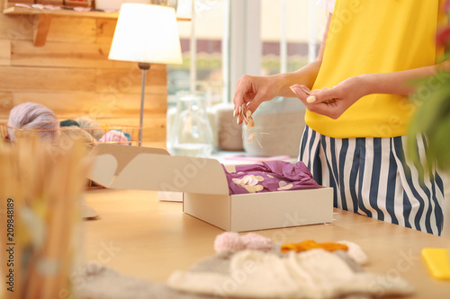 Foto Murales Yellow shirt. Enthusiastic needlewoman wearing yellow shirt decorating her package standing near wooden table with lamp
