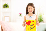 Little girl preparing greeting card for her mommy on Mother's Day at table - 209848312