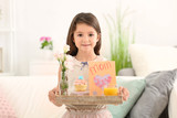 Little girl holding tray with breakfast and greeting card for her mommy on Mother's Day indoors - 209848314