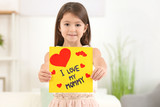 Little girl with greeting card for her mommy on Mother's Day indoors - 209848325