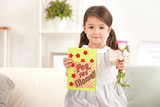 Little girl with greeting card and flowers for her mommy on Mother's Day indoors - 209848344