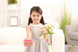 Little girl with gift and flowers for her mommy on Mother's Day indoors - 209848354
