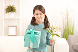Little girl with gift and flowers for her mommy on Mother's Day indoors - 209848358