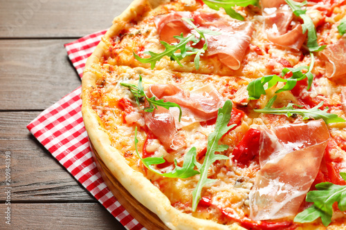 Leinwanddruck Bild Tasty hot pizza with meat on wooden background