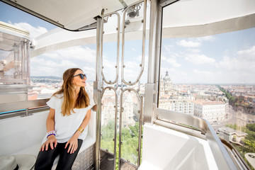 Young woman tourist enjoying aerial cityscape view from the ferries wheel in Budapest city, Hungary