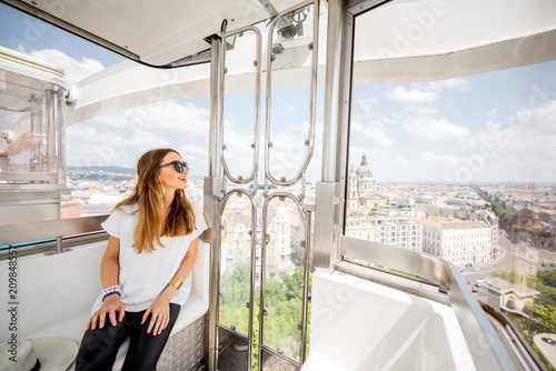 Foto Murales Young woman tourist enjoying aerial cityscape view from the ferries wheel in Budapest city, Hungary