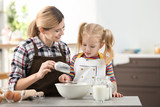 Mother with daughter making dough together in kitchen - 209848794