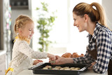 Mother with little daughter preparing cookies for baking in kitchen - 209848900