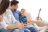 Happy family resting together on sofa at home - 209848922
