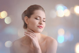 Portrait of beautiful young woman with soft skin after applying cream on blurred background - 209849342