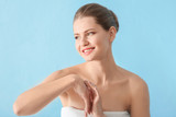 Young woman applying hand cream on color background - 209849390